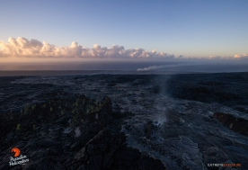 A large area of surface activity approaches Pulama Pali, just above where Jack Thompson's house used to sit. The newer flow is silvery in color, as opposed to darker older flows adjacent to it. The glowing spot in the middle of the frame is one of the skylights we observed, while the steam plume from the Kamokuna ocean entry is visible in the distance.
