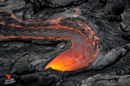 A river of lava pours from the ruptured crust of a tube, advancing the flow downslope.
