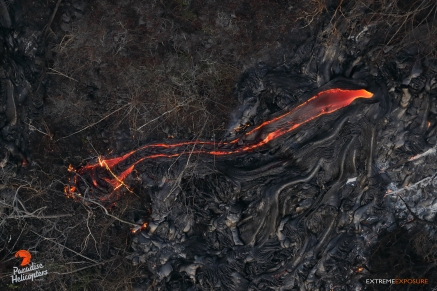 Molten lava consumes the dried remnants of toppled trees and brush from the flow's first pass through the kipuka.