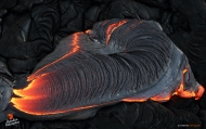A toe of ropey pahoehoe bleeds from the breakout's leading edge, its fresh, silvery surface contrasting with the jet black of the older flow it's overplating.