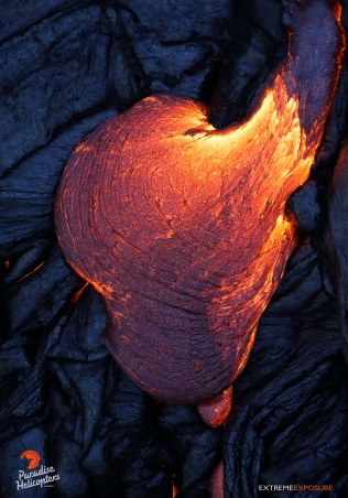 A toe of molten lava oozes forth and expands, its surface quickly darkening as it cools.
