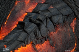 As lava moves from the bottom left to the upper right of the frame, the cooled skin floating mid-stream collects into those amazing fabric-like folds. This particular spot illustrates the process well.