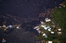The blue house still stands, but several neighbors' homes have been consumed over the past few days. An active lobe of lava pushes forth from beneath the crusty 'a'a flow field.