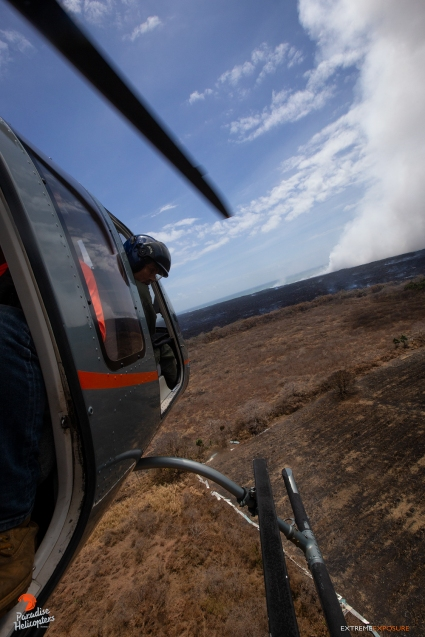 Cal expertly pilots the Bell 407, avoiding obstacles such as trees, shrubbery, fencing, and power lines, all while keeping an eye out for cattle. The steam plume in the distace is being generated by the ocean entry at Ahalanui, and is a mixture of steam, hydrochloric acid, and tiny bits of volcanic glass... a harmful mixture for humans as well as animals.